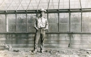 George posing in cowboy gear by a greenhouse, 1930s.